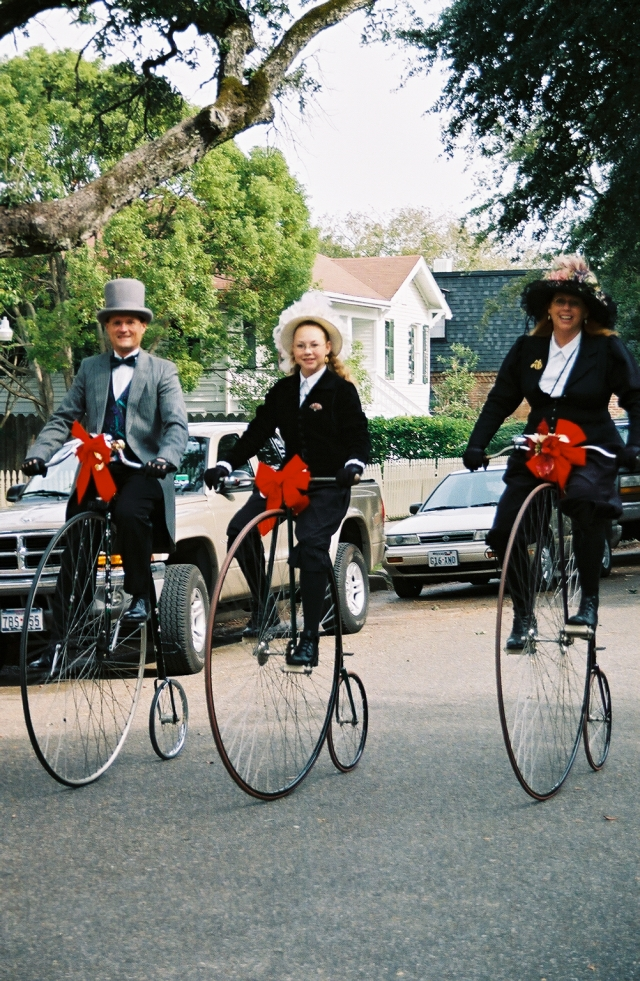 Three cyclists on Penny Farthing bicycles dressed in period costumes.
